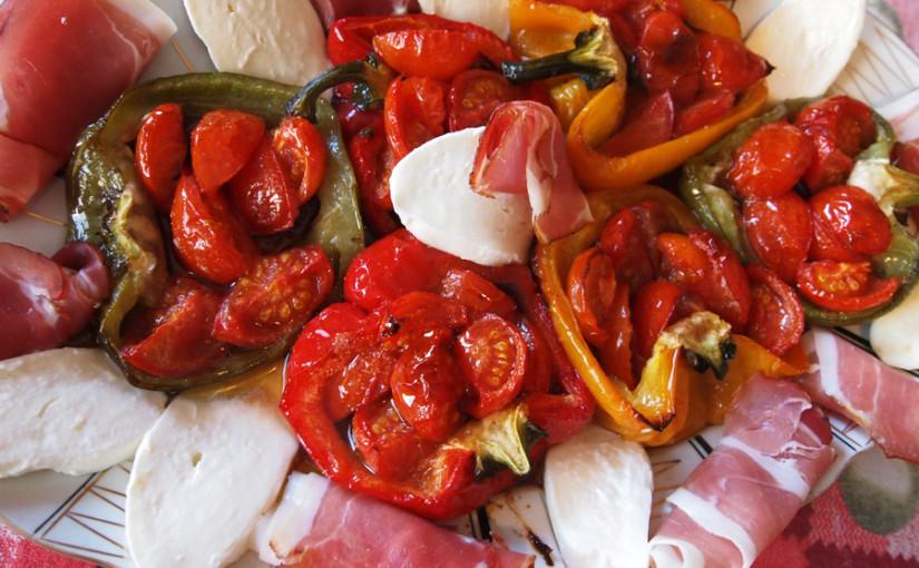 Пълнени чушки с домати и маслини, сервирани с прошуто и моцарела